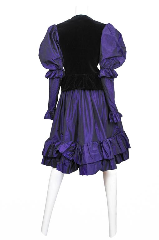 Vintage Yves Saint Laurent purple taffeta ensemble featuring a button front jacket with black velvet paneling in the front and back, purple puffed sleeves, and a matching purple taffeta skirt with a ruffle flounce at the hem. Circa 1982.