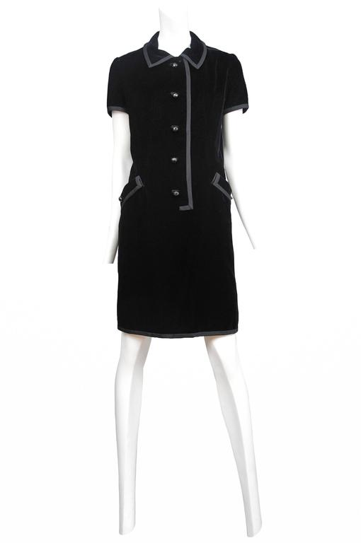 Vintage Yves Saint Laurent black velvet just above the knee smock dress featuring short sleeves, side pockets, five black buttons along the front closure and a finished collar. This garment has the Yves Saint Laurent Couture label with couture