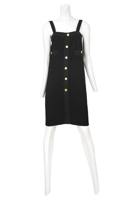 Vintage Chanel black shift dress featuring six gold buttons up the front button placket and two patch pockets at waist also featuring gold buttons.