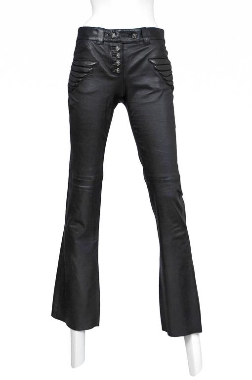 Vintage Alexander McQueen black leather pants with quilted skull patches at hips. Hipster fit, boot cut flare, and exposed button front. Circa 2000's.