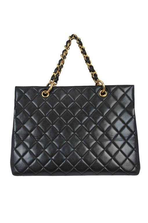 Vintage Chanel quilted CC purse in black lambskin featuring black leather interior lining, iconic leather and gold tone chain woven straps, large scale iconic interlocking CC's stitched on the front, one interior open pocket and one interior zipper