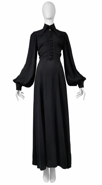 Vintage Ossie Clark black crepe gown featuring an elongated collar, bell sleeves, a tie at the back waist and a covered button front opening. Please inquire for additional images and measurements.