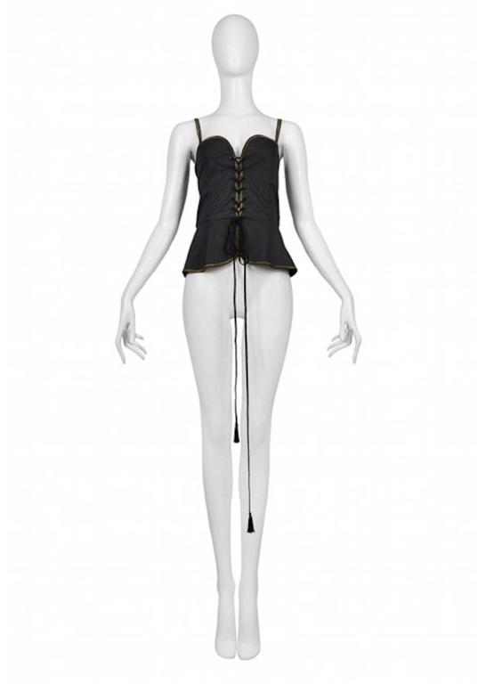 Vintage Yves Saint Laurent black safari corset tank featuring a built in peplum below the waist, gold rickrack trim along the edges and spaghetti straps, and tassel cording lacing up the front.