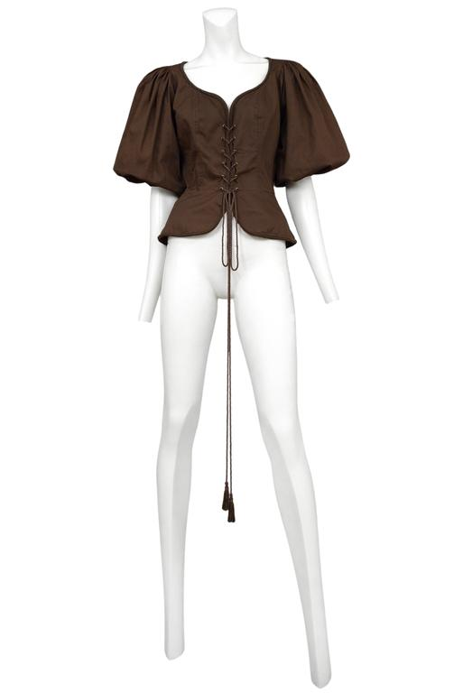 Vintage Yves Saint Laurent brown safari corset peasant top featuring a built in peplum below the waist, tassel cording lacing up the front and full peasant style sleeves. Please inquire for additional images.