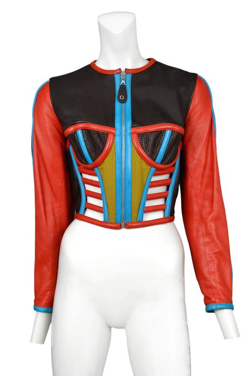 Vintage Jean Paul Gaultier iconic leather fitted moto jacket emulating a corset featuring red, turquoise, black and chartreuse leather, a zipper opening at the front, bra cups at the chest, faux boning at the waist and a snake emblem at the center