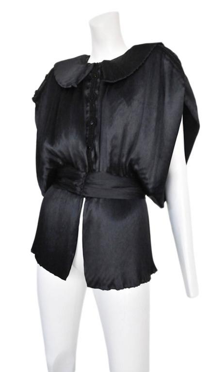 Black satin button down kimono inspired blouse with large round-cornered collar, waistband, and subtle pleated detail. Circa 1987. Please inquire for additional images.