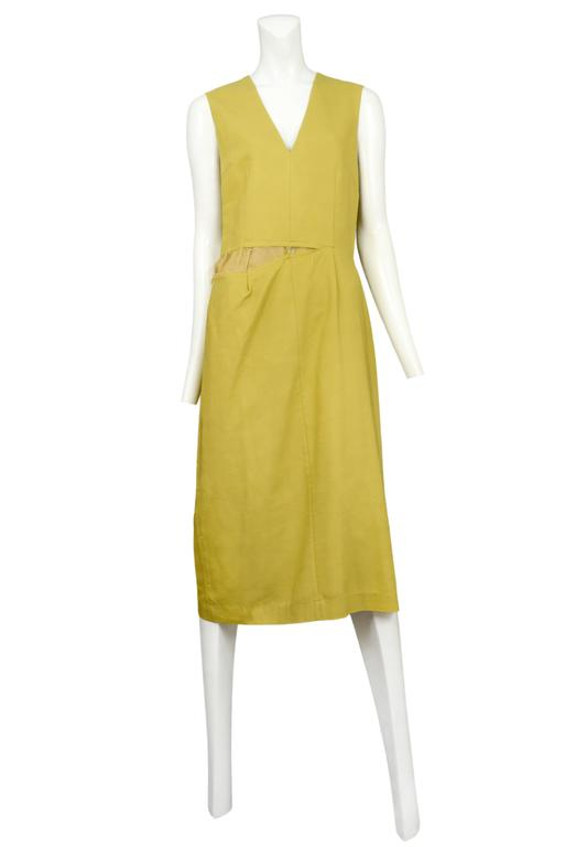 Vintage Maison Martin Margiela mustard yellow sleeveless below the knee dress featuring an intentionally ripped seam at the waistline, a v-neckline and a back vent at the skirt. Circa Autumn / Winter 2003. Please inquire for additional images.
