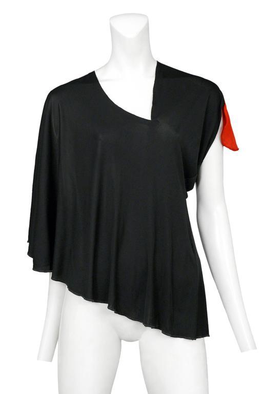 Vintage Maison Martin Margiela black asymmetrical cape top featuring a red cap at the left sleeve. Circa Spring / Summer 2007.