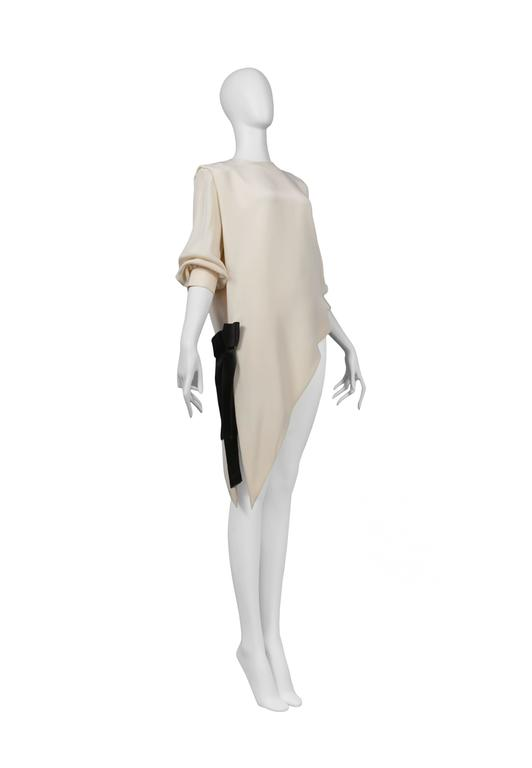 Pierre Cardin Couture off-white silk asymmetrical dress with black bow at hip. Circa, 1986-1993.