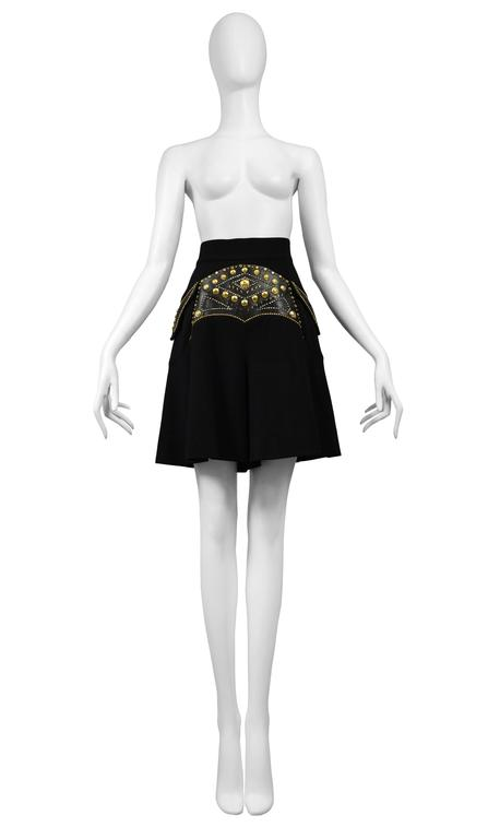 Vintage Versace black skort featuring leather paneling at the front with gold stud detailing.