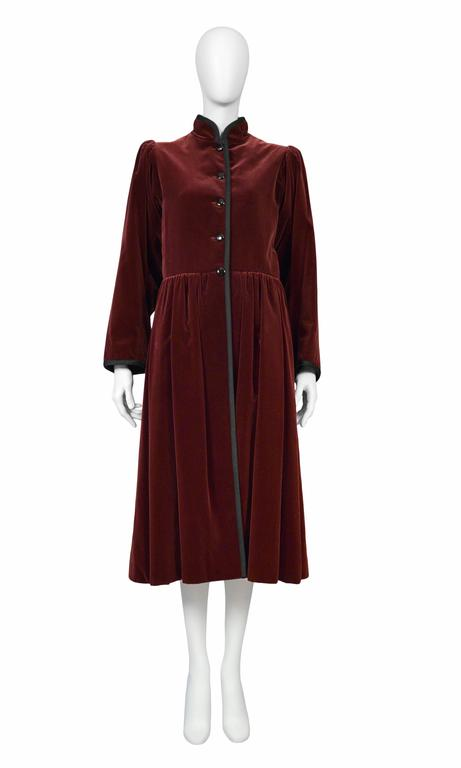 Vintage Yves Saint Laurent burgundy velvet long sleeve coat with black trim. Circa 1970s.