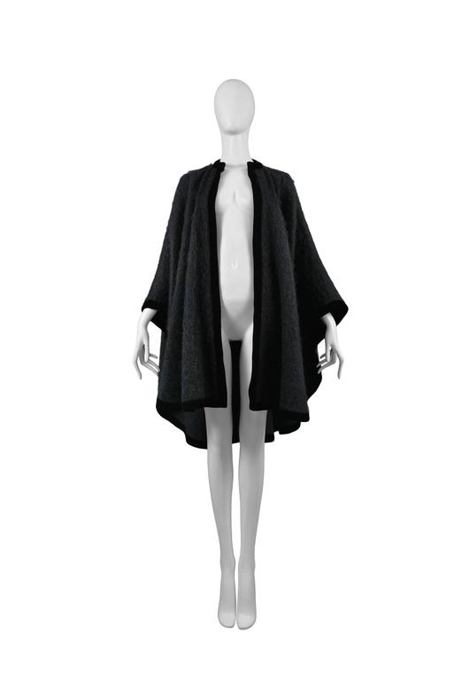 Vintage Yves Saint Laurent black mohair cape featuring velvet trim around the edges. Circa 1965.