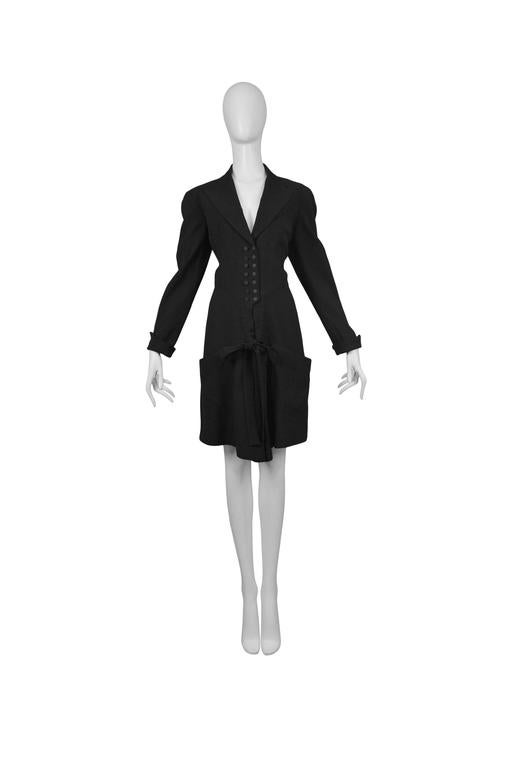 Black dinner suit shorts romper with covered buttons and bow tie front.