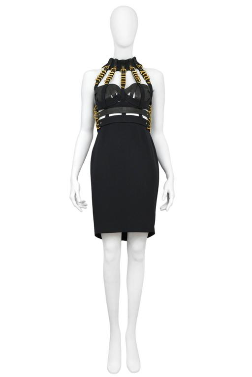 Resurrection is pleased to offer an important bondage dress from Gianni Versace's Fall 1992 collection, Miss S&M. The dress features a bondage style quilted bustier and skirt with gilt buckled straps. Tiny amber colored rhinestones decorate selected