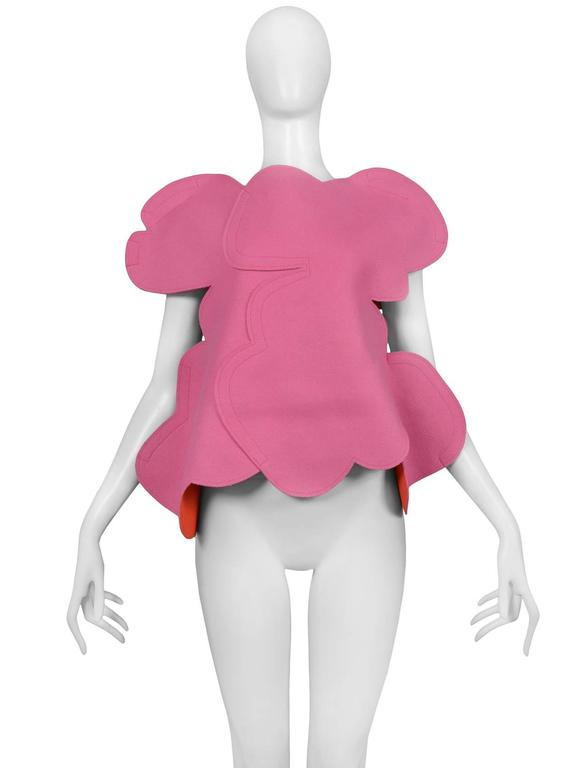 Comme des Garcons 2D bubblegum pink felt flat top. Top has circular motif and red interior insets. Collection AW 2012