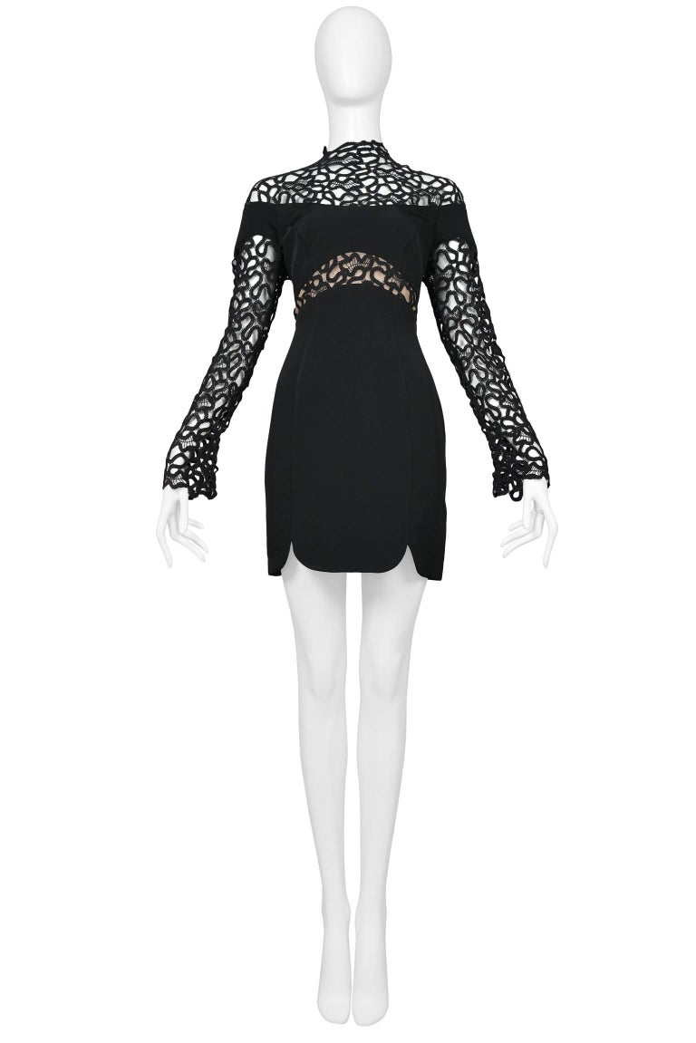 Thierry Mugler black squiggle lace and solid insets mini cocktail dress. The dress features a button up back, high neck, long sleeves, and a nude panel at center front. The skirt has two notches at front sides. Fitted body.