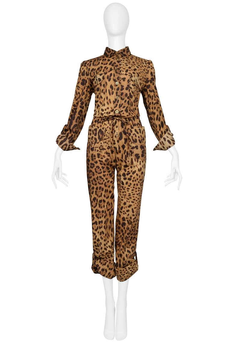 Dolce & Gabbana cotton leopard safari style belted jumpsuit with cargo pockets at front chest and hip, gold button front closure, cuff sleeves, and adjustable flap and button pant length. Slim fit and matching tie belt.