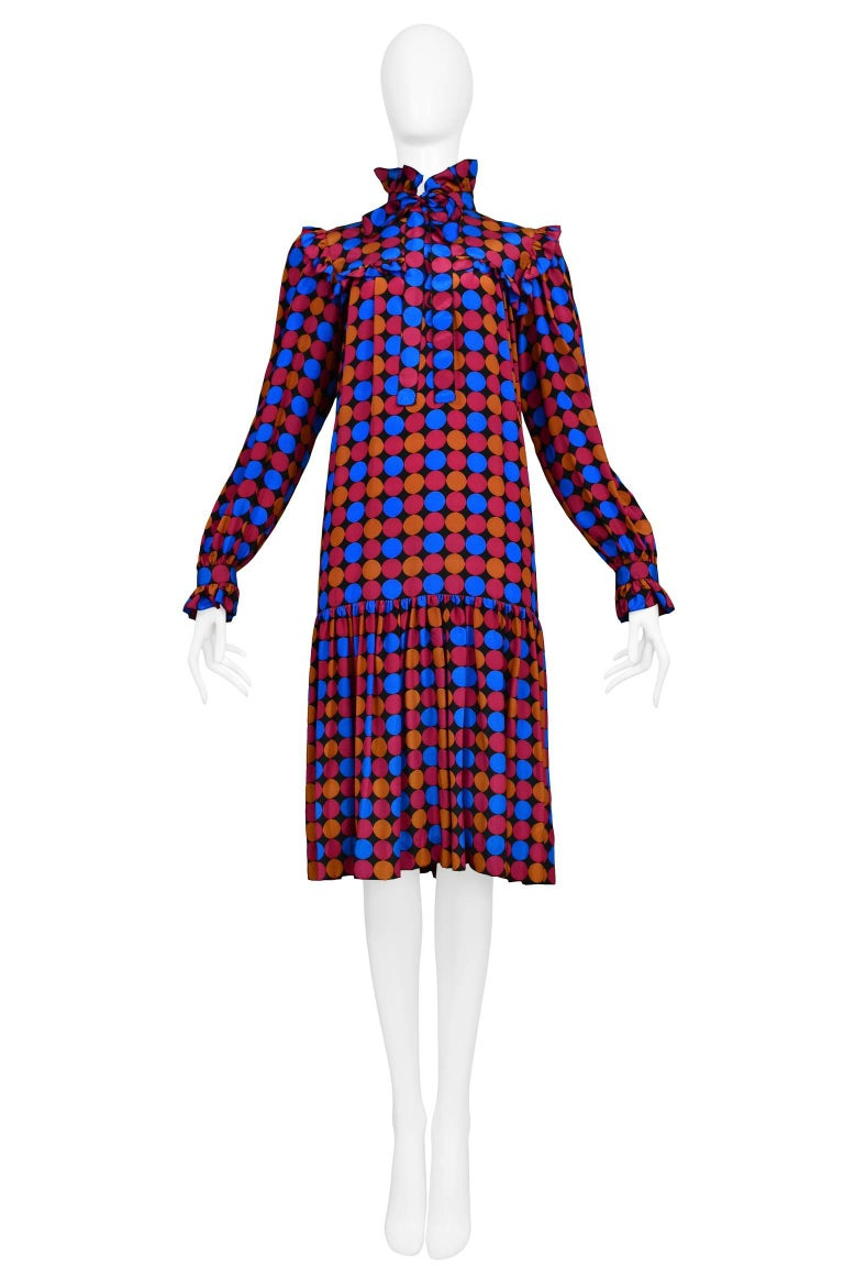 Vintage Yves Saint Laurent Day Dress featuring a drop waist, ruffle yolk and built in sash at the collar. The dress features an all over geo print of circles in magenta, blue and copper.