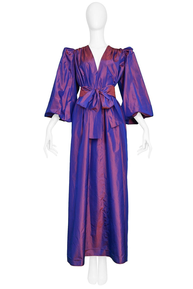 Vintage 1980s Yves Saint Laurent purple metallic taffeta gown featuring blouson sleeves with gathering at the shoulders, open neckline & sash that ties at the waist.   Excellent Condition.  Size: 40