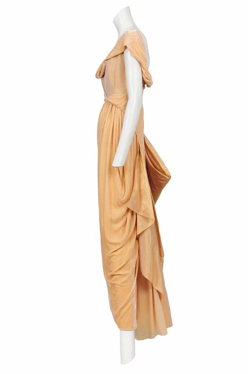 Vintage John Galliano peach iridescent taffeta and velvet drape gown featuring an asymmetrical cowl neckline, velvet drapery at hip and a covered button closure along the side.