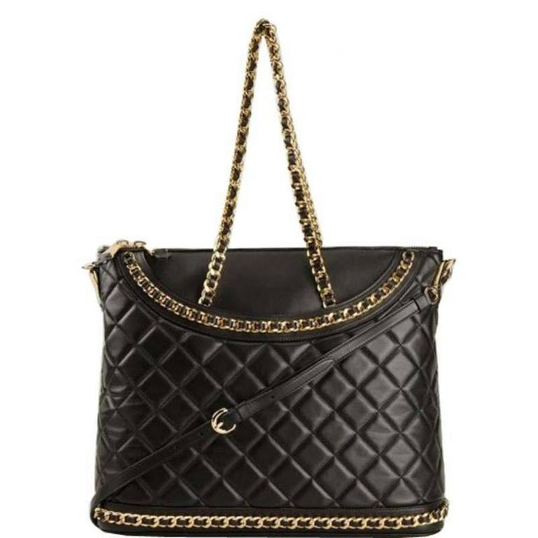 Black calf leather large quilted tote from Moschino featuring a detachable shoulder strap, a front logo patch, gold-tone chain trim, two gold-tone chain and leather top handles and dual top zip fastenings. Height: 32 centimeters, width: 39