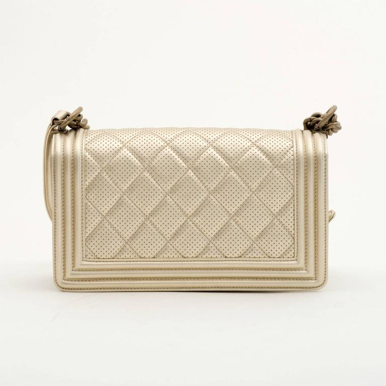 Chanel Perforated Quilted Leather Gold  Chanel Perforated Quilted Leather Gold perforated quilted leather with antique gold tone hardware. This bag features a full front flap with the signature Le Boy CC push lock closure and a chain link, and