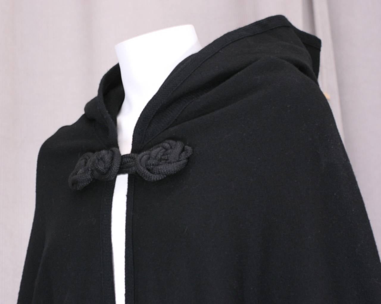 Half circle black wool melton cape with frog closure at neck. Large monks hood, completely edged in signature YSL soutache. The signature soutache was used in many YSL collections and is used on the hood, neckline, and all exposed edges. Cape is