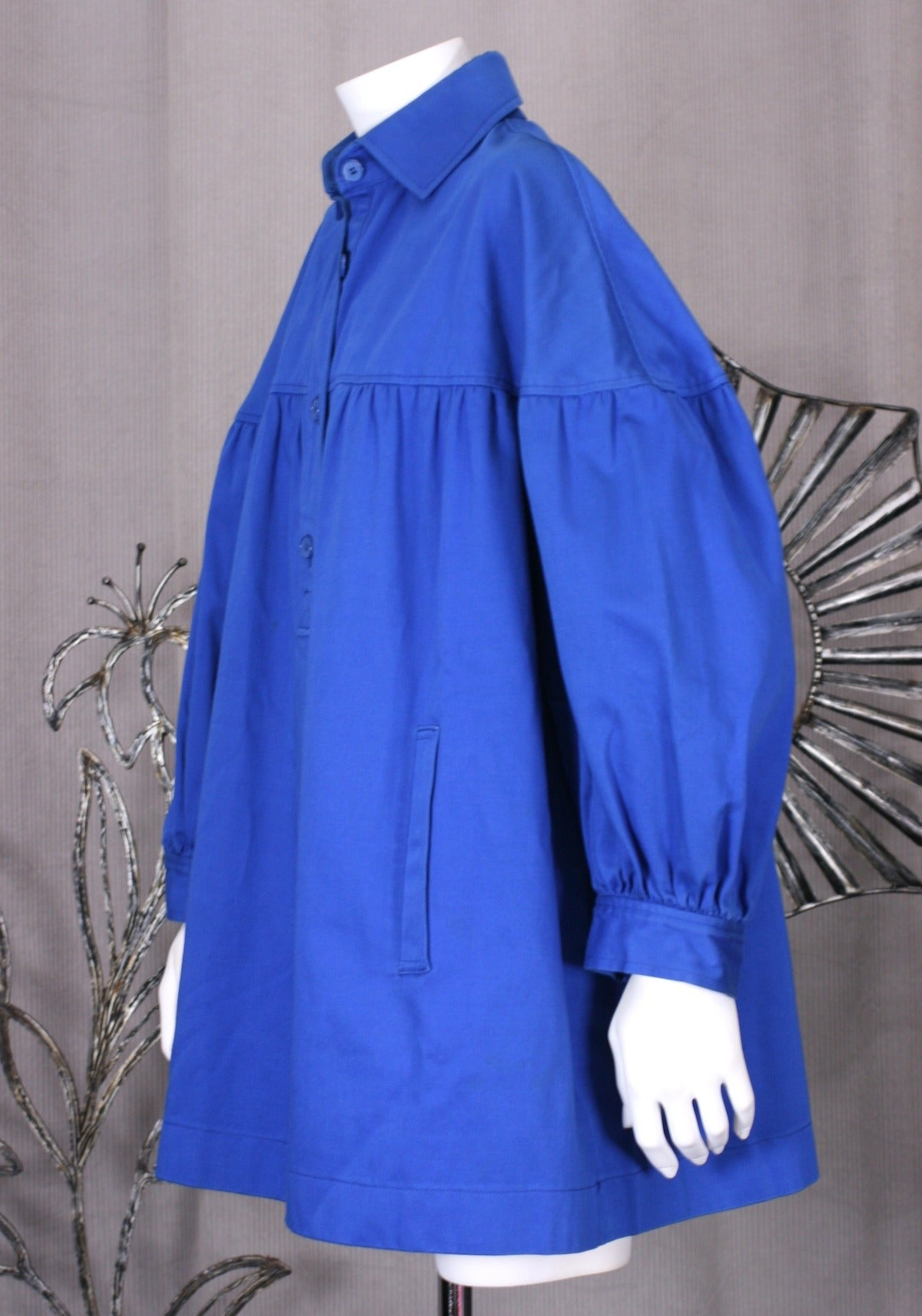 YSL French blue cotton twill blouse based on French peasant smocks. He has reproportioned the design elements of the blouse and added slash pockets. Front button placket with full gathered sleeves which end at a large cuff.