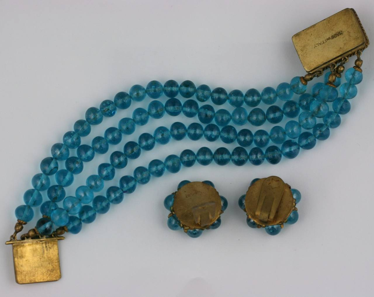 Coppola e Toppo Aqua Glass Demi Parure. Composed of dark aqua glass bead earclips and a four strand dark aqua glass bead bracelet with decorated gilt clasp. Excellent condition. Unsigned. 