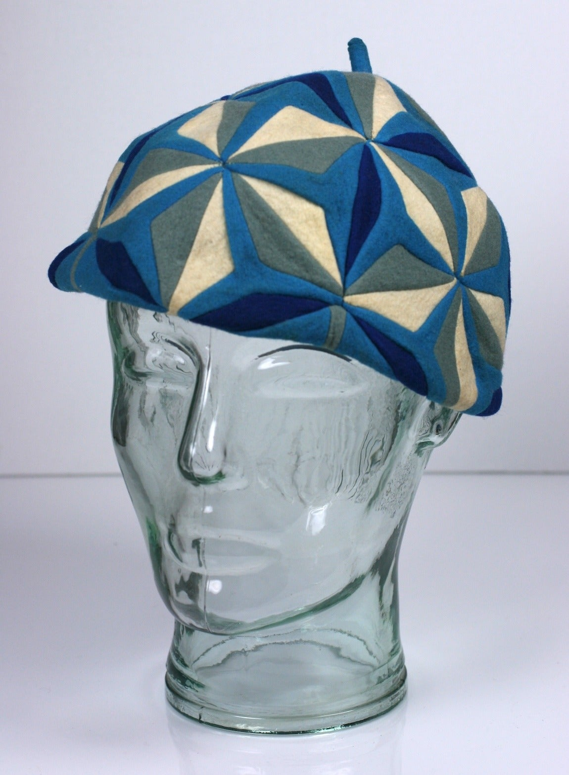 The Italian doll company Lenci occasionally made small fashion accessories such as this beret from the 1930's. This elaborate hand pieced patterning is highly evocative of Cubism and the Art Deco era in shades of blues, grays and white wool felt.