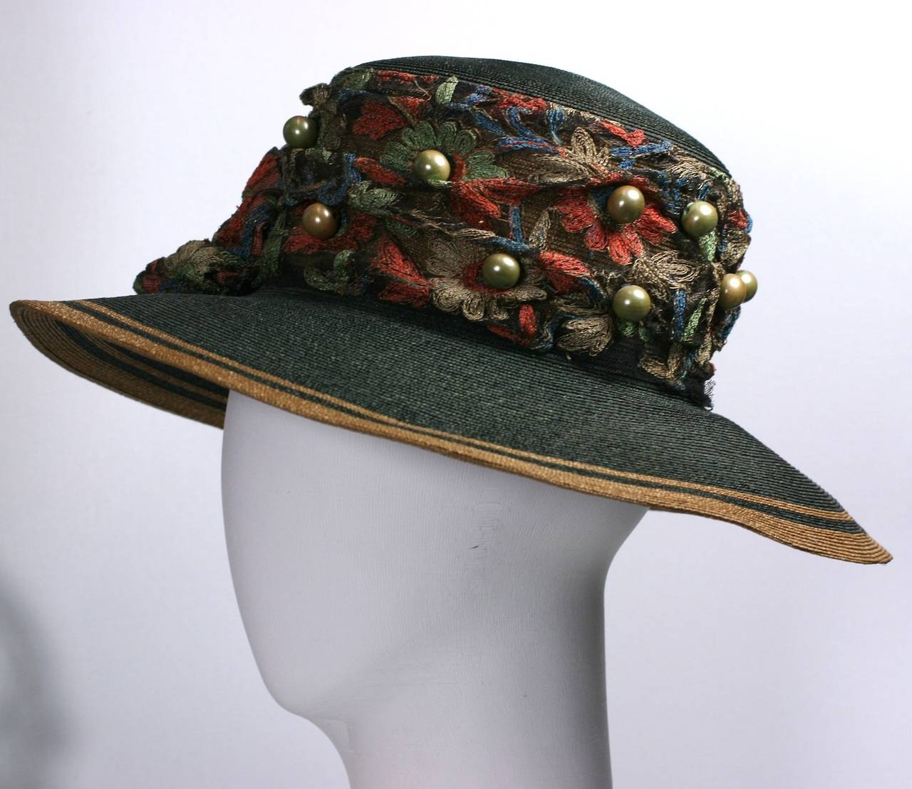 Edwardian straw hat with floral lace and large green faux pearls from the early 20th Century. 2 toned straw is decorated with a wide vibrant band of floral lace and 3 large lace rosettes. Large celadon faux pearls are strewn throughout. Black silk
