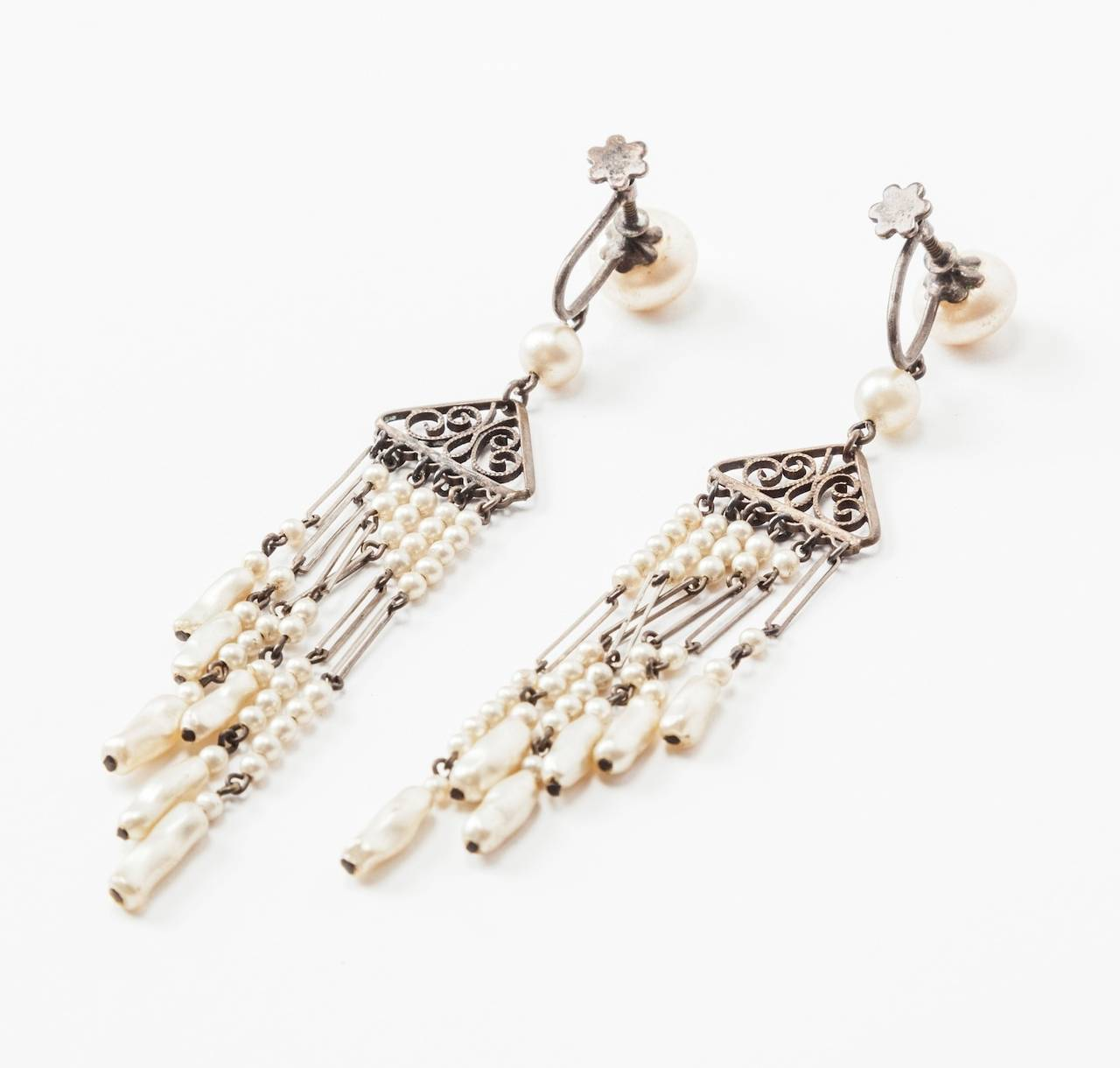 Delicate Art Deco faux pearl fringe earrings with filigree stations. Nicely detailed with both smooth and baroque faux pearls. 1920's USA. Sterling screw back fittings. Excellent condition.