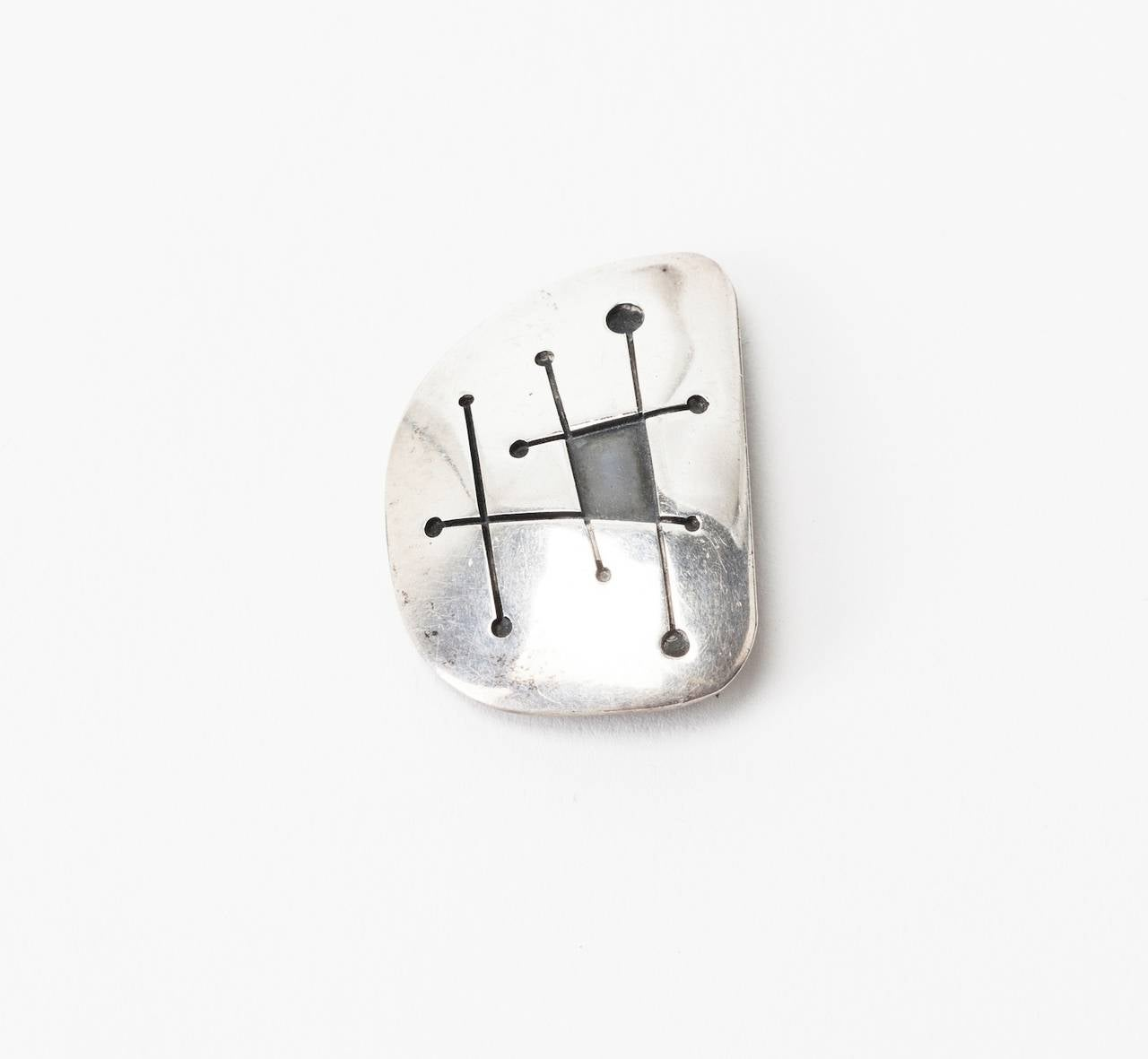Ed Weiner Modernist Brooch  constructed of 2 layers of sterling silver, the top cut away with 50's atomic, modernist motifs, then soldered to the base and patinaed for high contrast. a stunning example of 50's Modernist aesthetic. 1.5