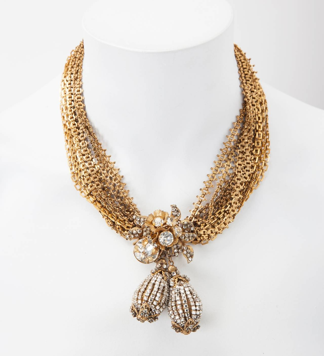 Miriam Haskell's elaborate signature Russian gilt multi chain necklace with intricate crystal pave work mounted on gilt filigrees. Focal pendant with double pear shaped pendant drops of hand sewn minute crystal rose montes falling from a floriform