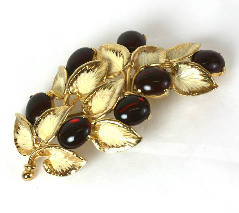 Schiaparelli's lovely garnet pate de verre cabocheon naturalistic berry branch brooch. Of gilt metal and ivory colored cold enamel.