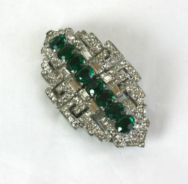 High style Trifari Art Deco Faux Emerald Clips from the 1930's. This pair of versatile Art Deco clips can be attached to a frame which turns them into one brooch, or they can be separated and used on a lapel or garment edge as sparkly decorations.