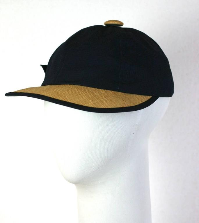 Charming 1950's raffia and navy seersucker cap by Kathleen Originals of Miami. Beach wear fashions of the 50's used unusual materials such as seersucker and raffia for both fashion and sun protection purposes. Crown 3.5