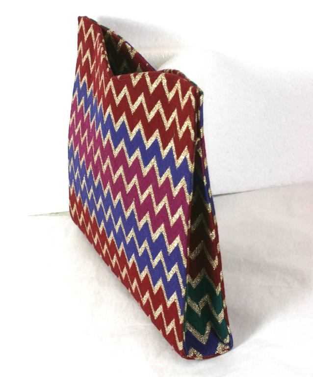 Missoni signature jersey knit clutch bag of gold lurex, burgundy, purple and magenta zig-zags motifs with vivid emerald green sides. Backed on a hard satin base with magnetic closures. 1980's Italy. Excellent Condition. L 10
