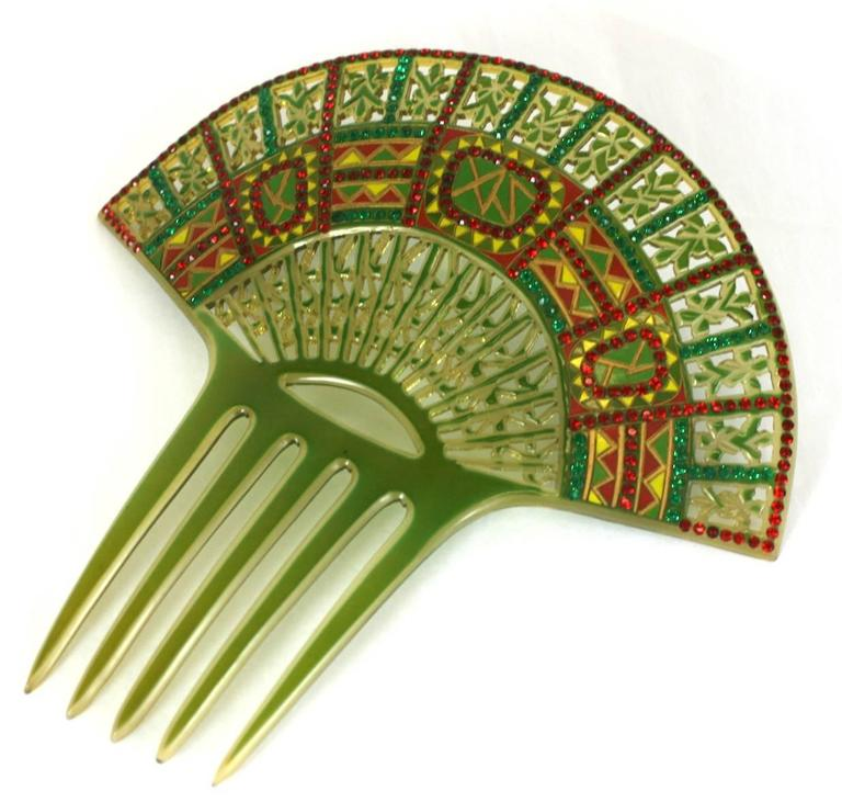 Wonderful Art Deco Eygptian Revival Comb of clear celluloid overlaid with green. The design is then pierced, overpainted and set with pave stones in red and green. France 1930's. 