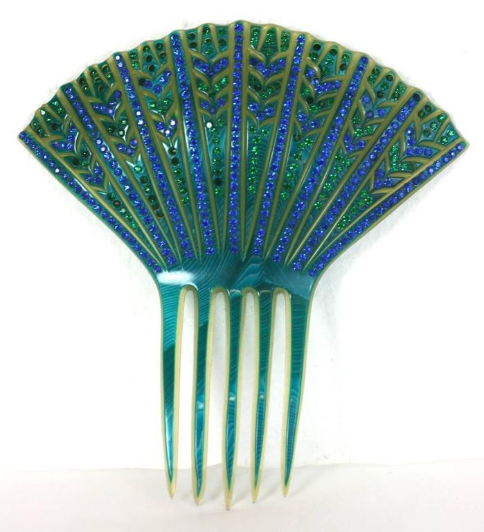 Fine French Art Deco Paste Comb made in France in the 1930's. Clear celluloid  is overlaid with a vibrant turquoise celluloid which is incised and carved away, then hand set with pave rhinestones in blues and greens. Delicate yet elaborate Art Deco