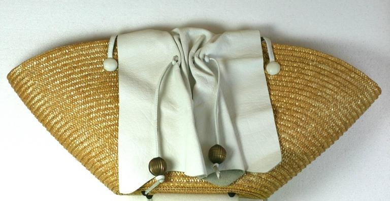 Carlos Falchi Oversized Straw Tote with signature gathered leather flap detail and ribbed ball decoration. Bag is lined in a gold textile with long shoulder straps in white leather. One snap interior closure. Made in Italy. 1980's USA.  27