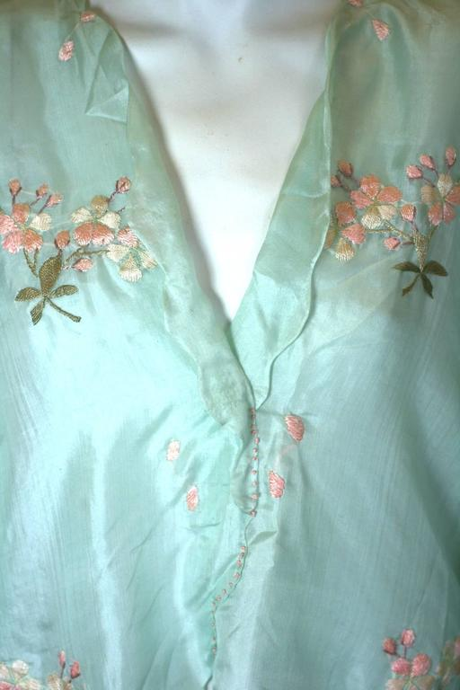 Edwardian china silk blouse of palest robins egg blue, hand embroidered with small bouquets of pink apple blossoms and leaves. Charming scalloped edges with a faux button tab on each side. Completely lined in same silk. Made in Japan for USA export.