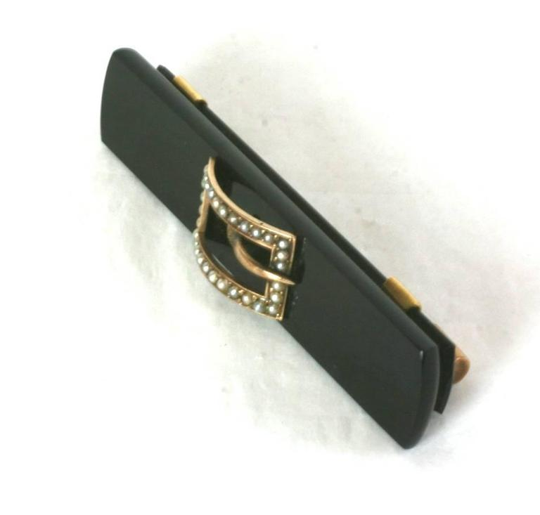 Timeless Victorian Onyx 14 kt Gold and Seed Pearl Buckle Brooch from the late 19th Century. 2.75