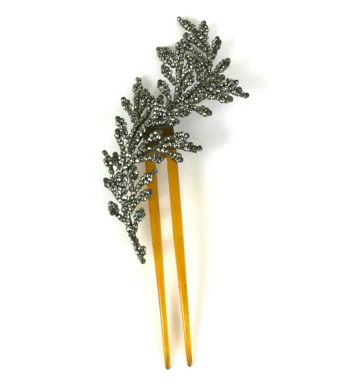 French Cut Steel and blond horn feather comb, the polished steel faceted studs riveted to a steel backing to create the feathers' form, with multiple layers and densely packed studs. The finer and older the piece, the more facets the studs will