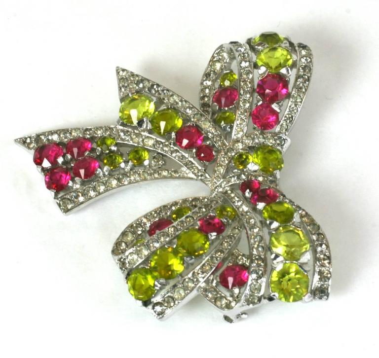 Exceptional Marcel Boucher Art Deco pave crystal, faux ruby and faux demantoid green garnet bow brooch. Lovely, unusual combination of colors for the period with a large, striking scale. High quality Rhodium finished metal, Marked: MB (phrygian