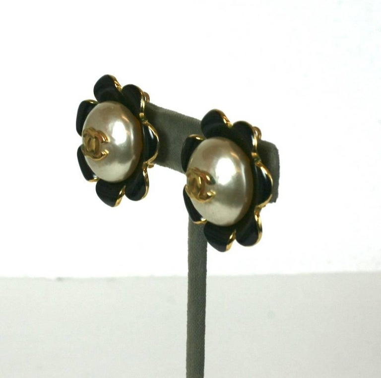 "Chanel Enamel Flower Logo Earrings from the 1990's. Enamel pop flowers are set with a Gripoix faux pearl and decorated with a gilt ""CC"" logo. 1.5"