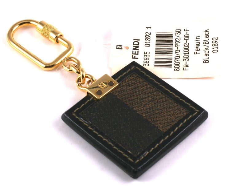 Fendi Logo Keychain from the 1990's with original tag. Branded on both sides, tag is made of leather with signature stripe textile on back.  5.25