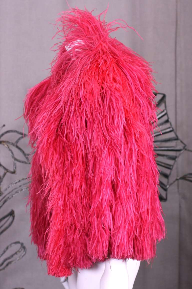 Glamorous vivid red cape from the Art Deco period of luxurious long plumes of ostrich feathers stitched onto a silk crepe base. The feathers sway beautifully when wearer moves. 1930's France. Retailed by Saks Fifth Avenue, NY in the 1930's.