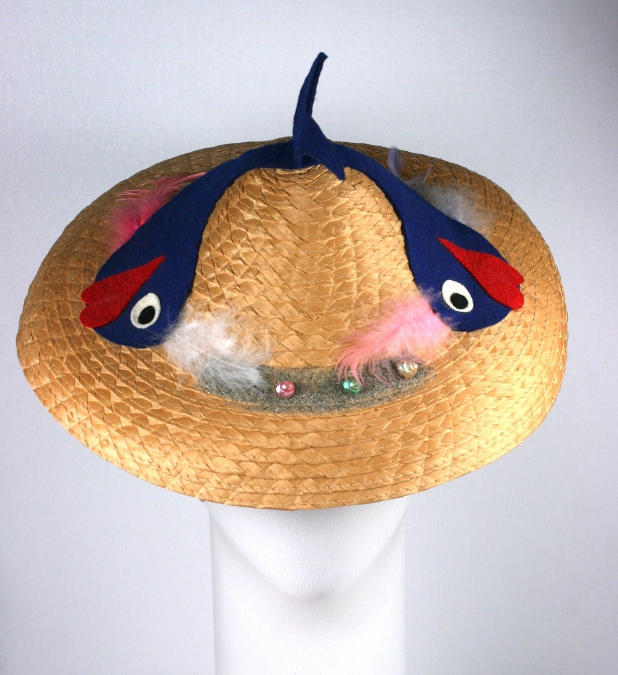 Amusing Italian Straw Beach Hat decorated with two charming felt cartoon baby whales with big grins. The whales' tails rises up out of the tip of hat. Further trimmed with seashells, mica glitter, and pastel feathers. Silly, charming 1950's Beach