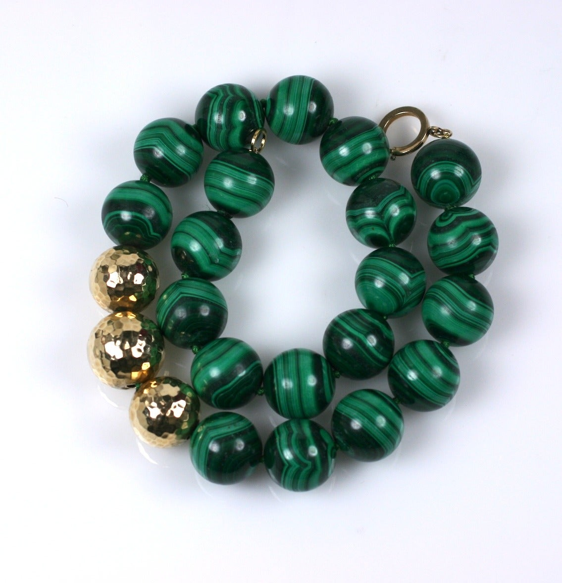 Oversized hand knotted Malachite beads are accented with 3 large hammered 14k gold beads. Attractive and wearable classic. Beads 20mm. Length 20